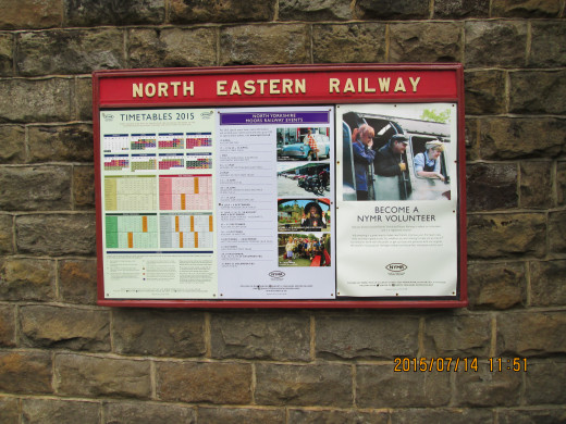 Notice board in the station yard with a recruitment poster for volunteers, other notices and NYMR timetable