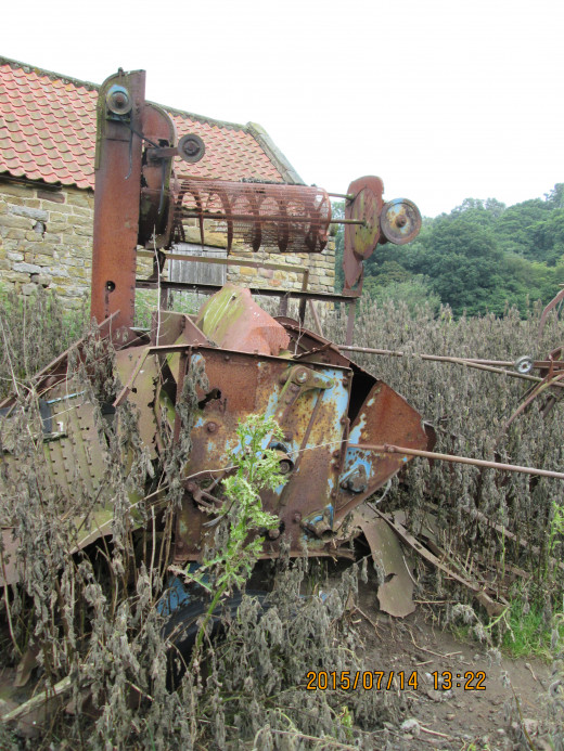 Abandoned agricultural machinery left outside a stone barn near the original Whitby & Pickering Railway (W&PR) trackbed