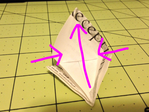This is probably the trickiest step. Fold the bottom up at the crease where you folded down that top triangle. In my mind I have always thought of this as a canoe. Then it will be easy to fold the sides down flat along the creases from the last step.