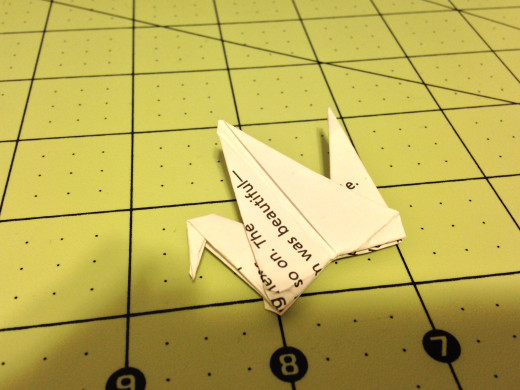 Fold the point down on one side to make the head. Then curl the wings outward.