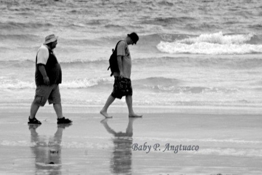 two men walking along the beach