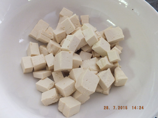 Take the drained tofu and chop it into bite size cubes.