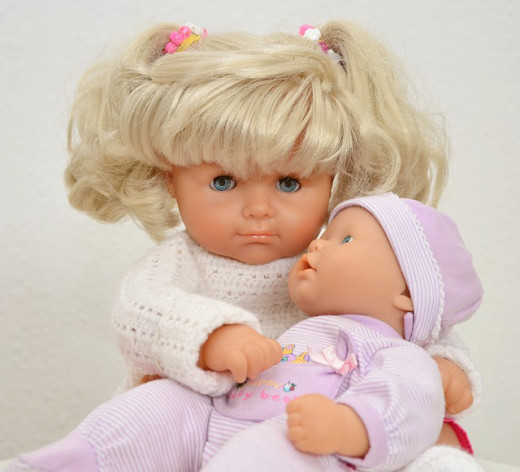 A little girl and her baby doll. Both are contemporary dolls.