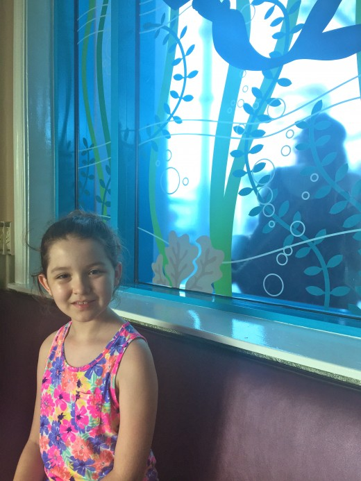 The birthday girl sitting in front of the Ariel window waiting to be seated.