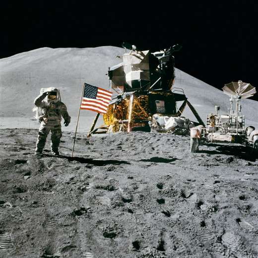 An astronaut of Apollo 15 standing on the surface of the moon with a USA Flag