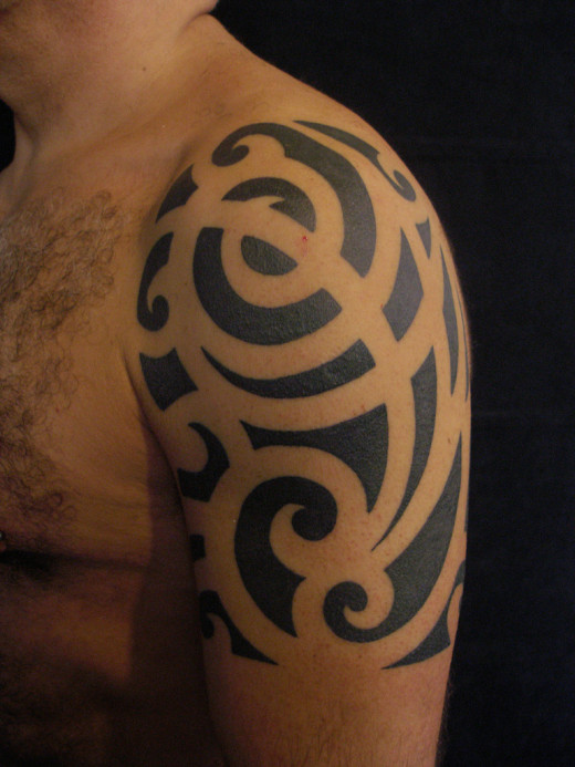 The thick black lines of a tribal-style tattoo are difficult to remove.