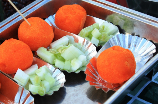 Deep-fried quail eggs (kwek-kwek) with chopped cucumbers on the side placed in oblong-shaped foil papers ready for serving.