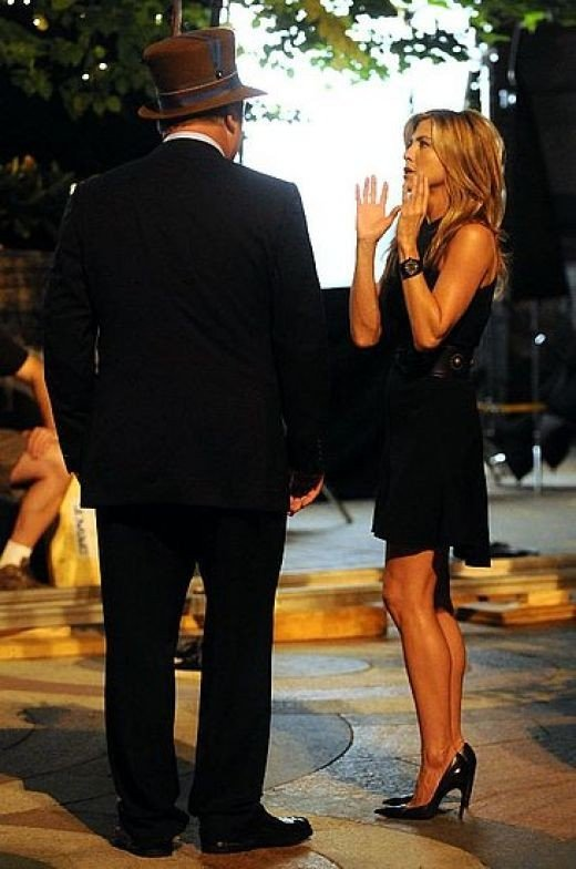 Jennifer Aniston in a dress and high heels on the 30 Rock TV set
