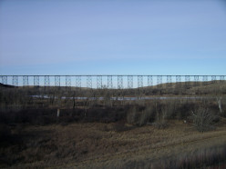 A photograph of the Lethbridge Viaduct at midday. Photograph taken from the south of the viaduct, near Whoop-up Drive, on the west side of the Oldman River.