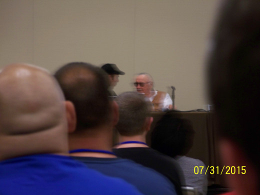 Stan Lee's staff member repeating a fan question to him.