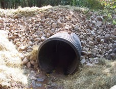 """Notice the dark material in the culvert. Many times the material consists of """"black sand"""", hematite, magnetite, lead and other heavier metals that collect along with gold."""