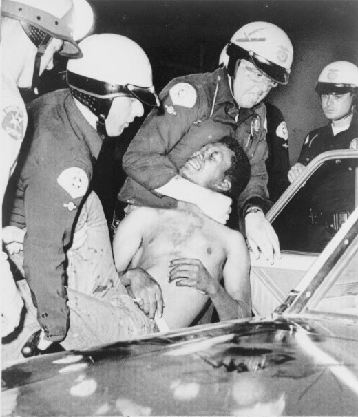 Police arrest a man during the Watts Riots
