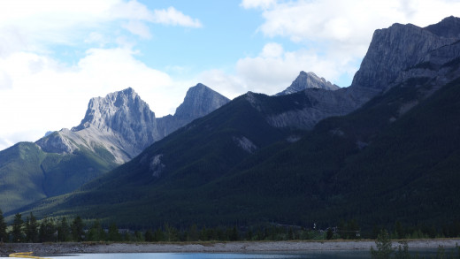 River walk, picture of the Bow river bank with the Three Sisters peaks in the background. Canmore, Alberta, Canada