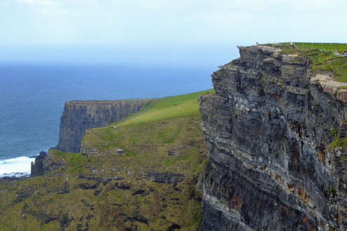 The two tiny specks at the edge of the cliffs along the horizon are people who display the massive scale of Moher. © Scott Bateman