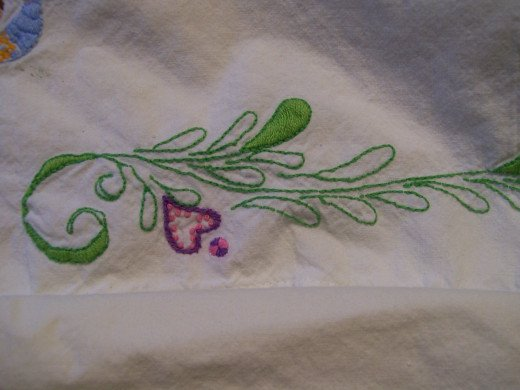 Close up of embroidered greenery on embroidered pillow case.