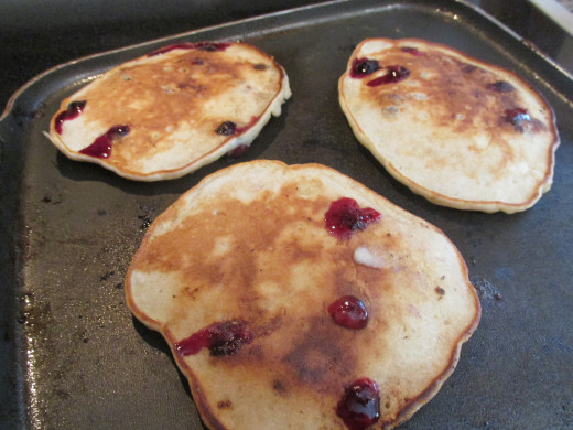 Pancakes on the grill bursting with blueberries.