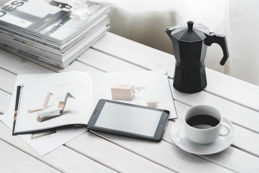 Outside desk with coffee and mobile tablet.