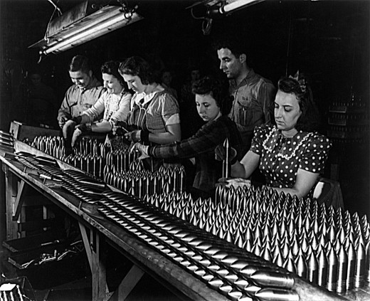 Women work alongside of men in this Midwest aluminum factory now converted to production of war materials. These young workers are assembling 37mm armor-piercing shot prior to heat treating operations