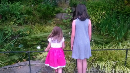 My friends two little girls in front of a lily pond in the rose garden Warwick Castle