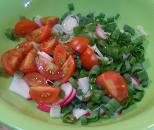Adding tomatoes, green onion and radish to salad