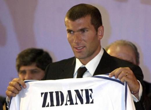 Zinedine Zidane holding Real Madrid jersey.