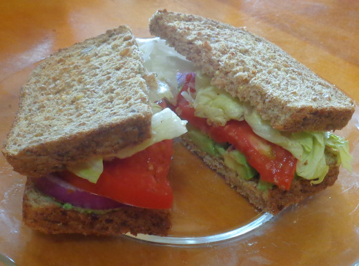 Avocado sandwich with tomato, onion and lettuce on sprouted whole grain bread