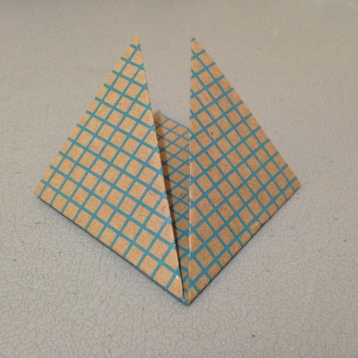 Fold each outside corner up so the point touches the top. When flat it looks like a diamond.