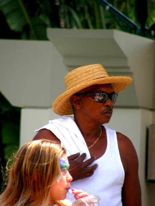Attendee at the festival keeps cool with a straw hat, shades and towel.