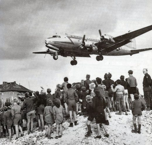 Crowds watch as a USAF C-54 lands at Berlin Tempelhof with supplies during the Blockade
