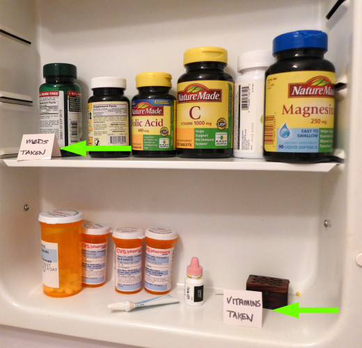 "Flip up ""pills taken"" sign(s) and stand them on the OPPOSITE shelf. (For example, if prescription bottles are on the bottom, put the ""meds taken"" sign on the top shelf.)"