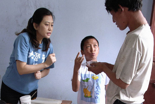 A volunteer talks with a patient in a leprosy-plagued village in Taiwan