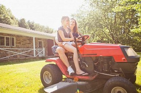 A mom gives her daughter lessons on how to cut grass.