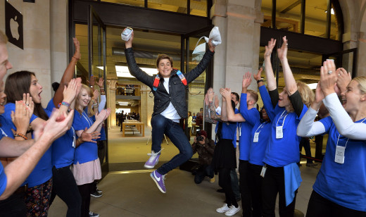 A customer clicks his heels in celebration as he is one of the first to obtain the latest Apple product, applauded by Apple Store Staff.