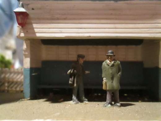 A couple of passengers in the open-fronted shelter, waiting (picture was taken facing backwards, as the shelter front looks away towards the goods depot opposite)