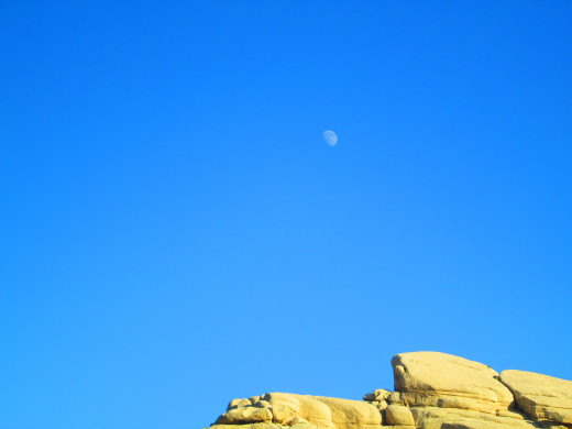 The moon above the boulder formation.