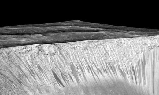 Dark narrow streaks called recurring slope lineae emanate out of the walls of Garni crater on Mars. Photograph: Nasa/AFP/Getty Images