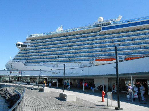 The Royal Princess docked at Ponta Delgada in the Azores with stores and restaurants in front of the ship.
