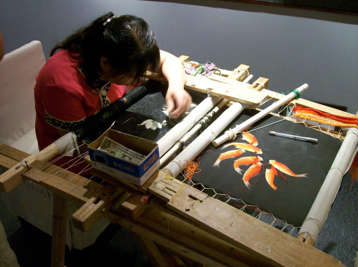 A woman working on a silk picture.