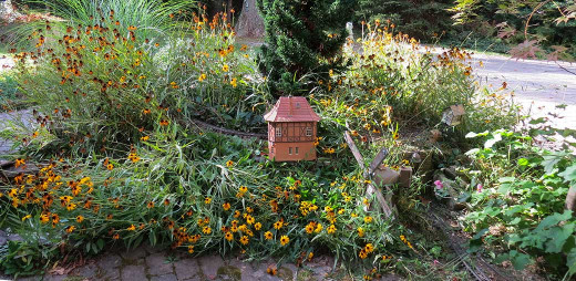 "The Swiss lodge looks grand amid Black Eyed Susans (Latin name, ""Rudbeckia hirta""). Yellow finch visitors soon arrive!"