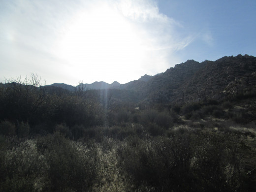 The rays of sunlight add dimension to the chaparral and boulder covered hills.