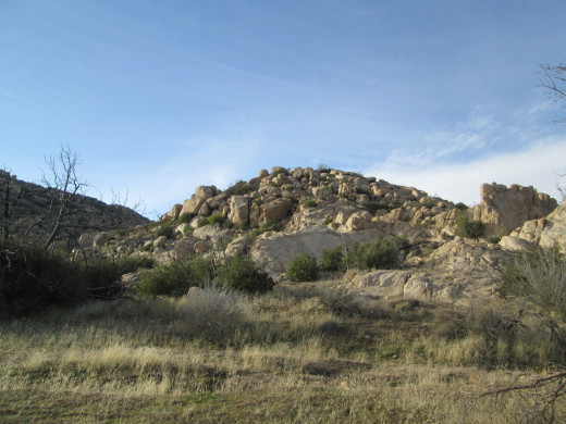 Yucca plants and chaparral bushes grow among the large boulders.