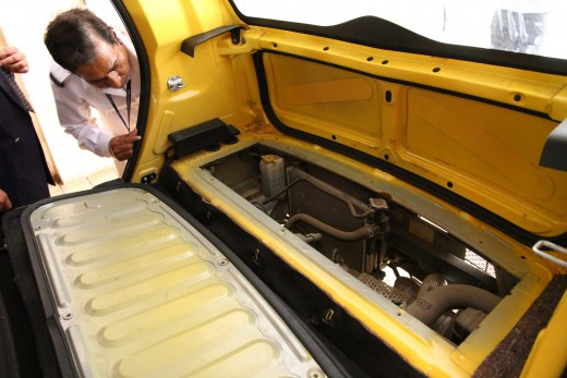 Tata Nano engine in the trunk that's only accessible from inside as a cost reduction feature. The back seats have been removed to reveal the engine in this photo.