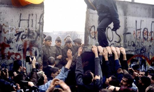 Berlin Wall falling, under the gaze of East German police.