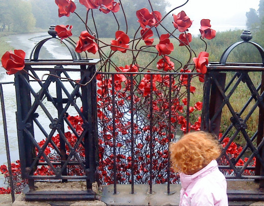 A little girl next to the poppy sculpture Wave.