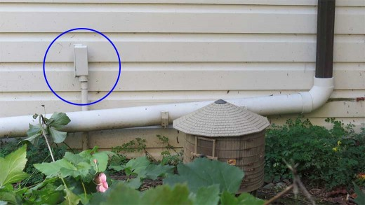 Outside conduit (circled) for low voltage wiring. PVC pipe redirects rainwater from gutter.
