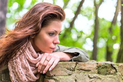 Woman in the park facing sadness.
