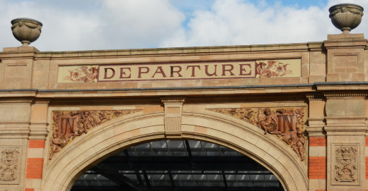 "The Wyvern emblem of the Midland Railway sit on both sides of  the ""DEPARTURE"" entrance."