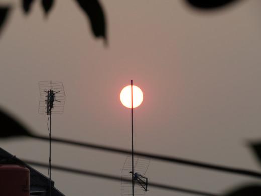 Pierced sunset seen from upper floor of my house.
