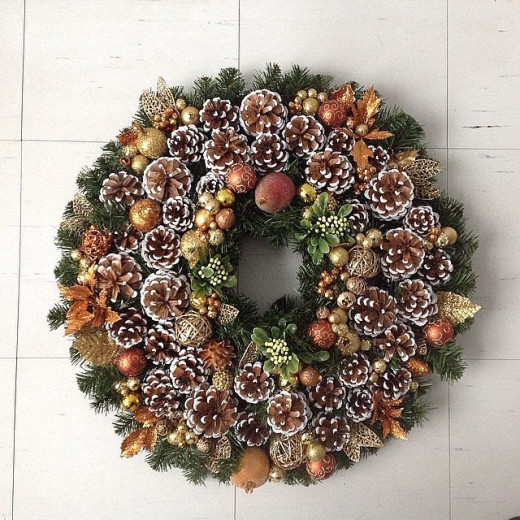 This wreath looks lush with bronze, gold, and rustic accents, such as pine cones.