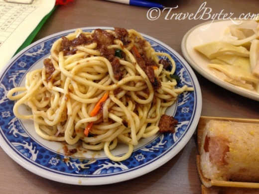 A plate of noodles with braised sauce: Springy noodles with braised sauce drizzled over